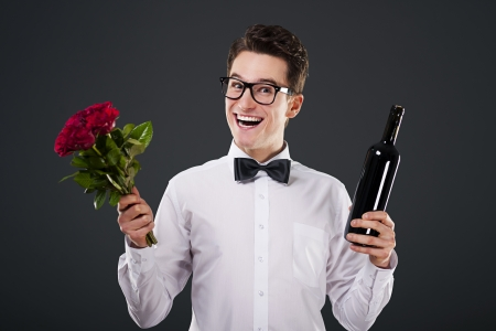 Happy man with a bouquet of roses and wine photo