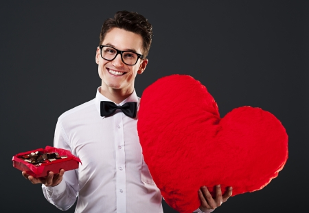 Man holding heart shape and box of chocolate photo