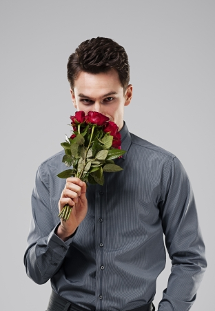 attracive: Handsome man smelling bouquet of red roses Stock Photo