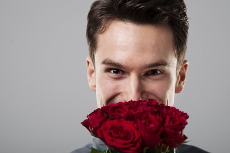 Cute man hiding behind flowers photo