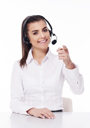 Woman with headset pointing at you photo