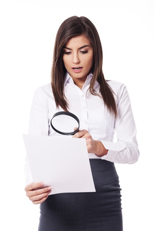 Shocked woman looking through a magnifying glass on documents Stock Photo - 18527183