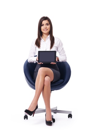 Sitting businesswoman holding a blank digital tablet with black screen photo