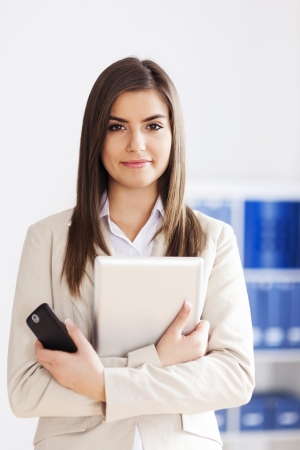 business wear: Young businesswoman holding digital tablet and mobile phone