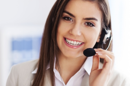 call center representative: Happy female wearing headset and looking at camera