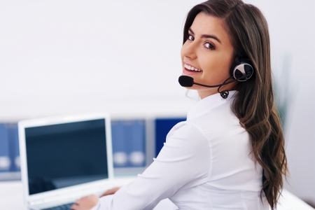 call center office: Young female operator with headphones Stock Photo