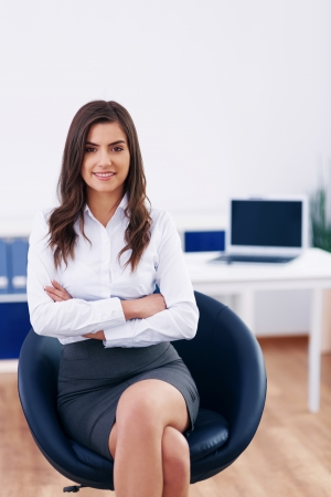 arms chair: Young businesswoman in office Stock Photo
