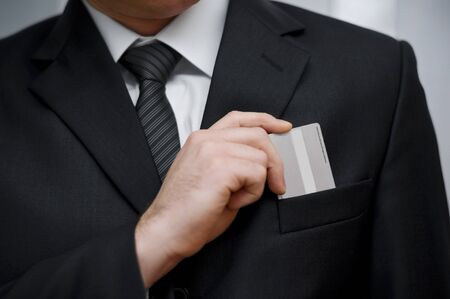 Businessman putting his credit card in pocket photo