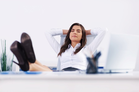 Young businesswoman relaxing in office photo