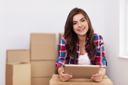 Young woman using digital tablet during moving in new apartment photo