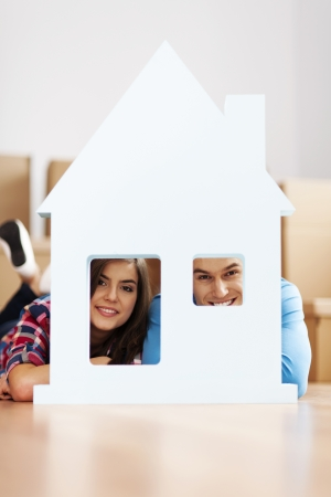 family moving house: Happy couple with home sign