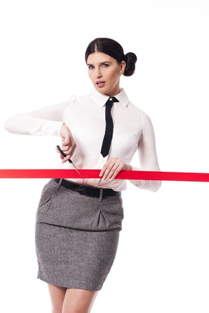 Serious and focus businesswoman cutting a red ribbon photo