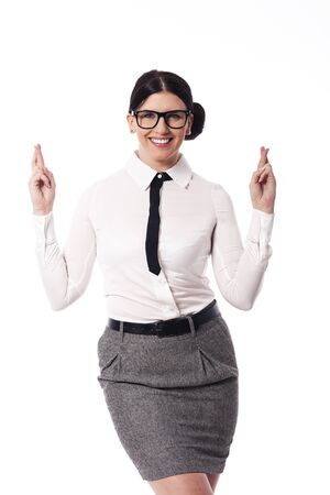 crossed fingers: Happy woman wearing glasses with crossed fingers Stock Photo