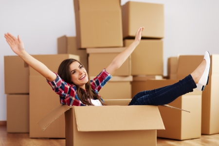 moving activity: Cheerful woman sitting in a cardboard box