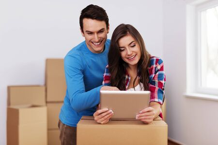 Young and loving couple arranging relocation in new home photo
