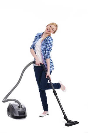 stereotypical housewife: Pretty and smiling woman vacuuming a floor