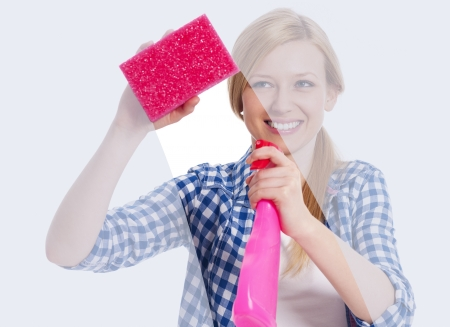 window cleaning: Young woman standing behind window and washing it Stock Photo