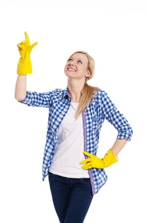 woman pointing up: Smiling female cleaner pointing up