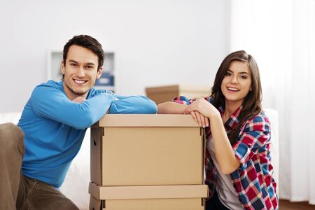 Portrait of young couple with moving boxes photo