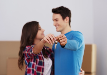 house keys: Young couple holding key to new home in hand Stock Photo