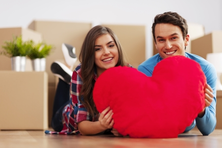 Young couple holding a heart shape in their new apartment photo