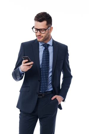 confident man: Handsome businessman checking emails on the phone Stock Photo