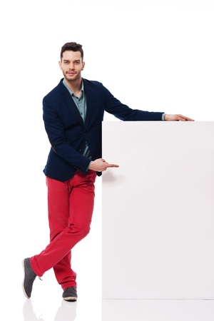 man pointing up: Young and handsome male pointing at blank billboard