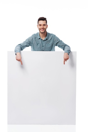 billboard posting: Happy young man pointing at empty board