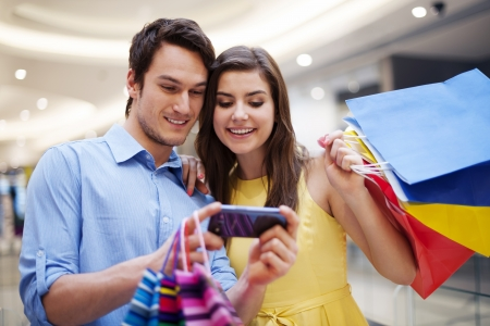 mobile shopping: Smiling couple looking at mobile phone