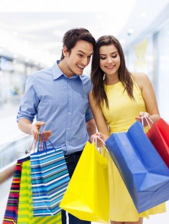 shopaholics: Surprised man peeking into shopping bag