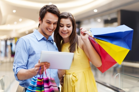happy shopping: Happy couple using s digital tablet in the shopping mall Stock Photo