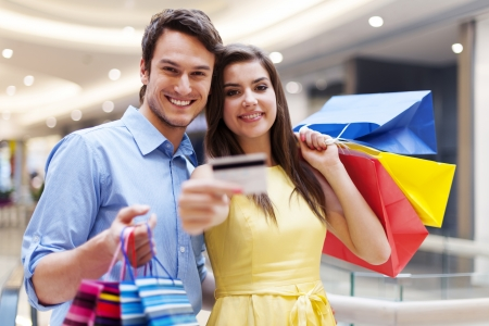 Beautiful couple showing credit card in the shopping mall  Stock Photo