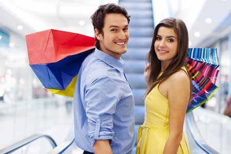 shopaholics: Smiling couple on escalator in shopping mall Stock Photo