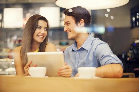 coquetear: Coqueteando pareja en el caf� utilizando tableta digital