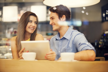 adult dating: Flirting couple in cafe using digital tablet