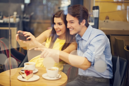 people on phone: Happy couple taking photo in cafe