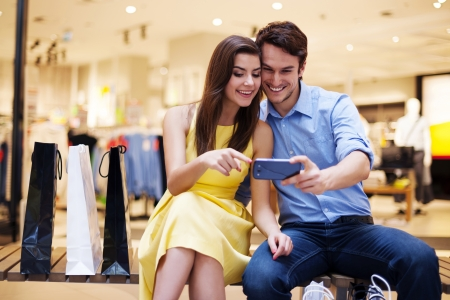 shopping man: Smiling young couple looking at mobile phone Stock Photo