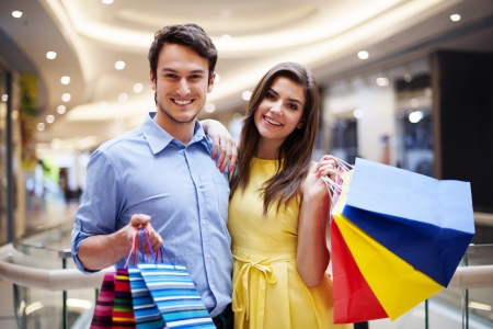 Portrait of happy couple with shopping bags Imagens
