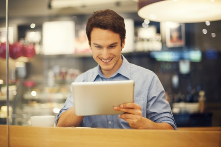 Smiling man using digital tablet in cafe  photo