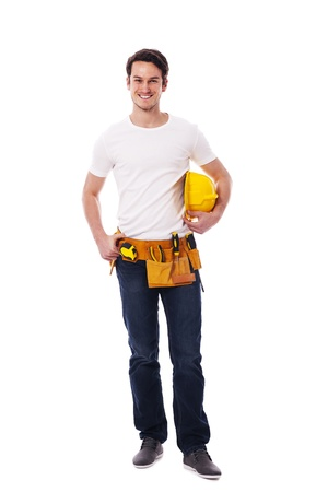 Smiling manual worker holding yellow hardhat photo