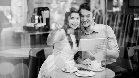 Happy couple in cafe holding digital tablet  photo