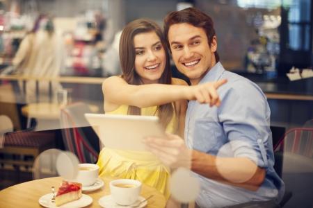 mujer tomando cafe: Mujer joven feliz que apunta a algo mientras est� sentado en el caf�
