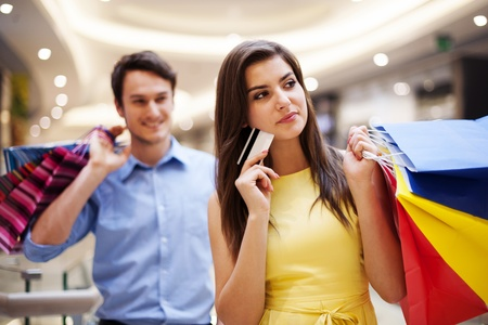 Focus young woman holding credit card and shopping bags photo