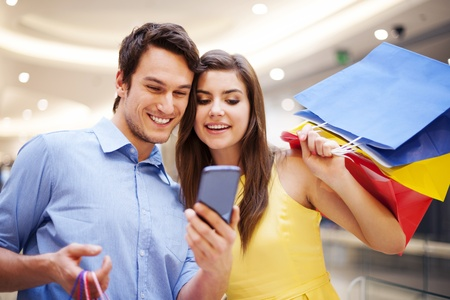 mobile shopping: Smiling couple checking something on the mobile phone Stock Photo