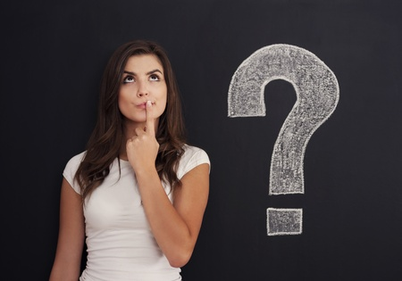 unsure: Woman with question mark on blackboard Stock Photo