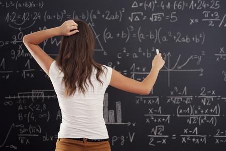 confundido: Mujer joven que mira el problema de matem�ticas en la pizarra Foto de archivo