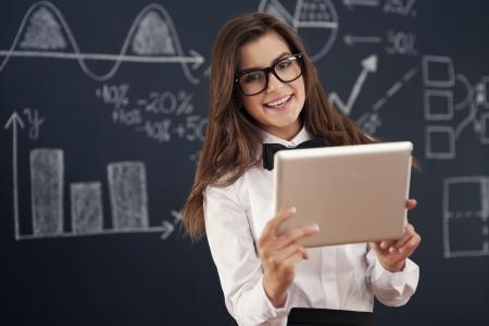 teacher student: Profesor sonriente que usa la tableta digital en el aula Foto de archivo