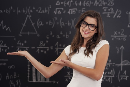 Woman wearing in glasses showing mathematical formulas photo