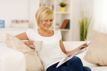 Blonde woman relaxing at home with coffe and newspaper  photo