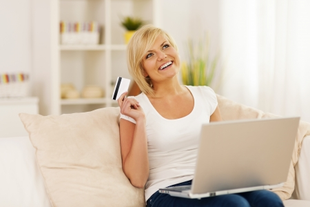 Smiling young woman using laptop and holding credit card photo
